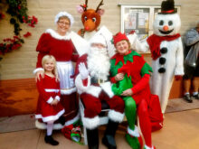 Pictured from left to right: Caitlyn Ortbahn – Mr. & Mrs. Claus' Granddaughter, Julie Ortbahn (and real Grandmother to Caitlyn) – Mrs. Claus, Santa – Bill Carpenter, MJ Clement – Rudolph the Red Nose Reindeer, Merrie Crawford – Elf and Wanda Johnson – Frosty the Snowman. Running around in the crowd somewhere was Elf Joyce Recupido.