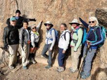"Club hikers giving a ""Thumbs Up"" at the top of Tom's Thumb. Pictured (left to right) are Brian Hill, Tim Allen, Mei-Mei Ahlskog, Dena Brinkman, Diane Alessi, Jeannette Chenier, DeEtte Faith, and Marilyn Harkins. (Photo by Warren Wasescha)"