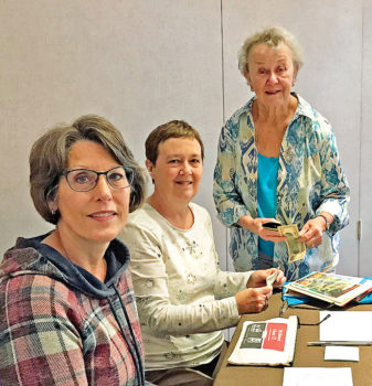 Pam Schulstad (standing) is stocking up on Crystal Cards with the help of volunteers Karen MacFarlane and Carol Norvet.