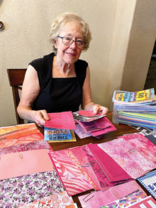 Working at home, Bobbie Reed chooses colorful trim paper for creating Crystal Cards.