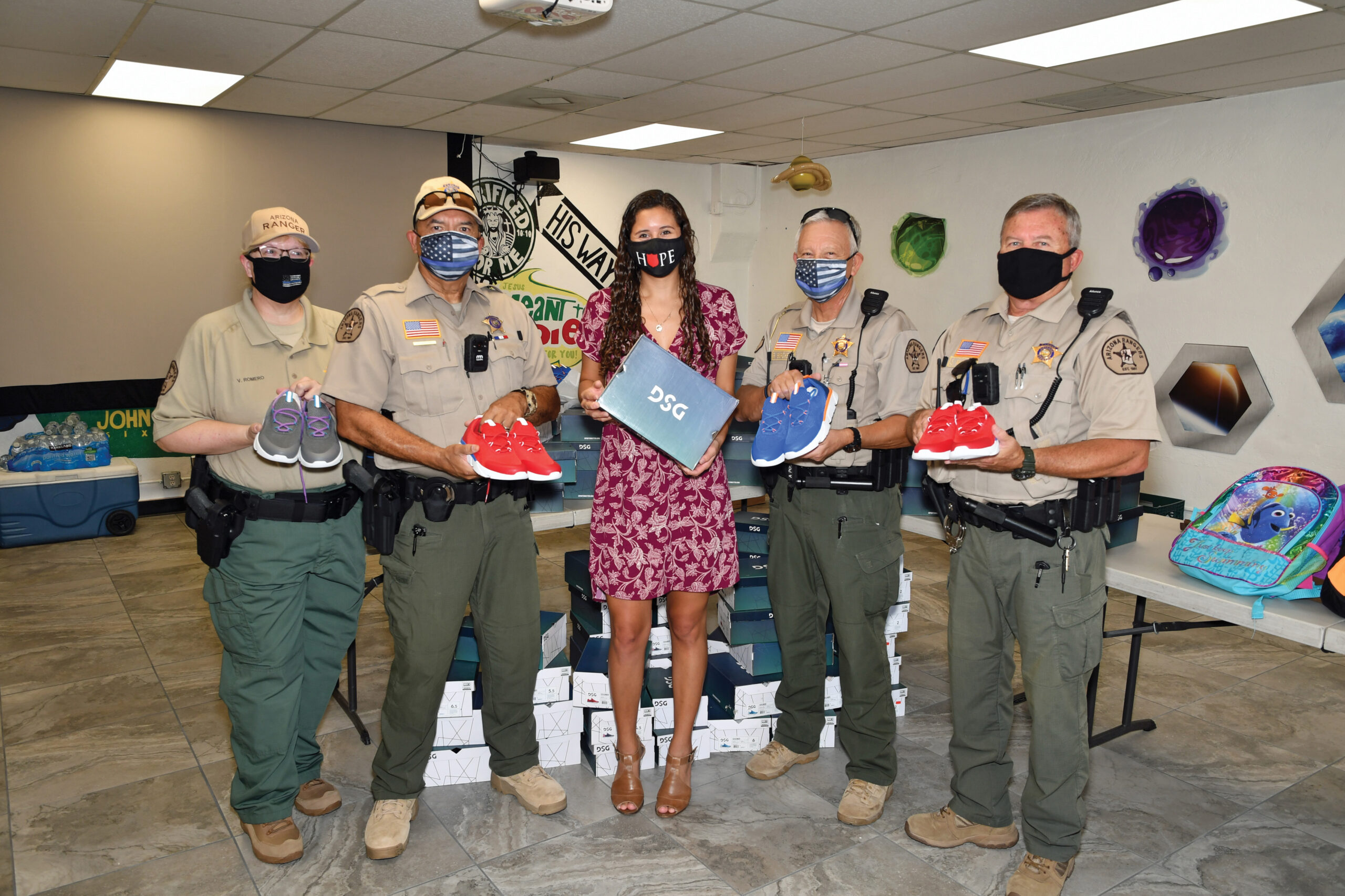 Left to right: Ranger Victoria Romero, Internal Affairs Officer Carlos Lozano, Neighborhood Resources Marketing and Special Events Coordinator Rori Minor, Company Commander Ron Buchett, and Executive Officer Scott Murdock display a sampling of shoes delivered to Chandler Neighborhood Resources.