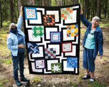 Outgoing President Sue Bart and her neighbor Maureen Sherman are shown displaying Sue's quilt. We asked Sue to remove her face mask for the picture. Look, they both have on jackets. Ah, to be cool again!