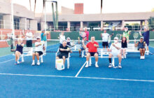 Teachers and students prepare for Cottonwood's free tennis clinics. Front row (seated): Karen Daugherty, Les Schick, Pierre Moresi (director with bucket of balls), Jerry Higgns, and Jim Southerland; second row (seated): Dick Kane, Joseph Fleming, Bonnie DeGrenier, and Sonda Giles; standing (left to right): Al Wagner (instructor), Ollie Johnson, Lucia Fleming, Cannon Hill, Jack Veit, John Arhangelsky, and Ken Griffin