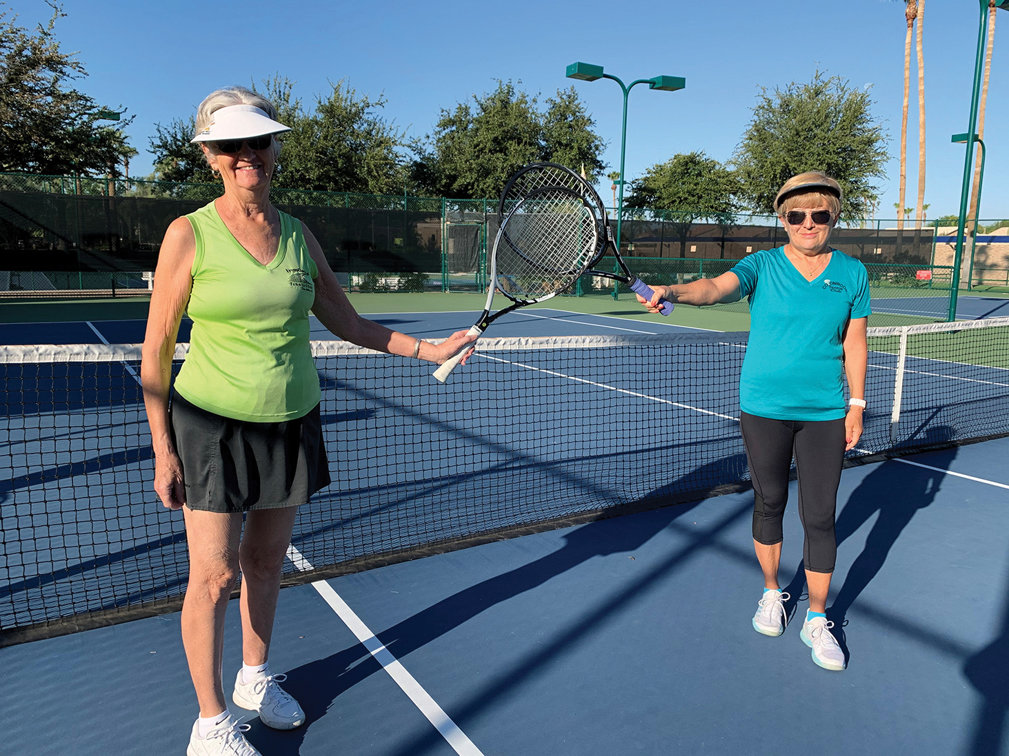 Vivian Guimond and Edith Tanniru warm up for the tennis mixer while social distancing.