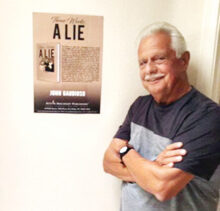 John Gaudioso with a poster of his book Three Weeks, a Lie