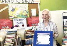 Suellen Eyre receiving an award with her book display.