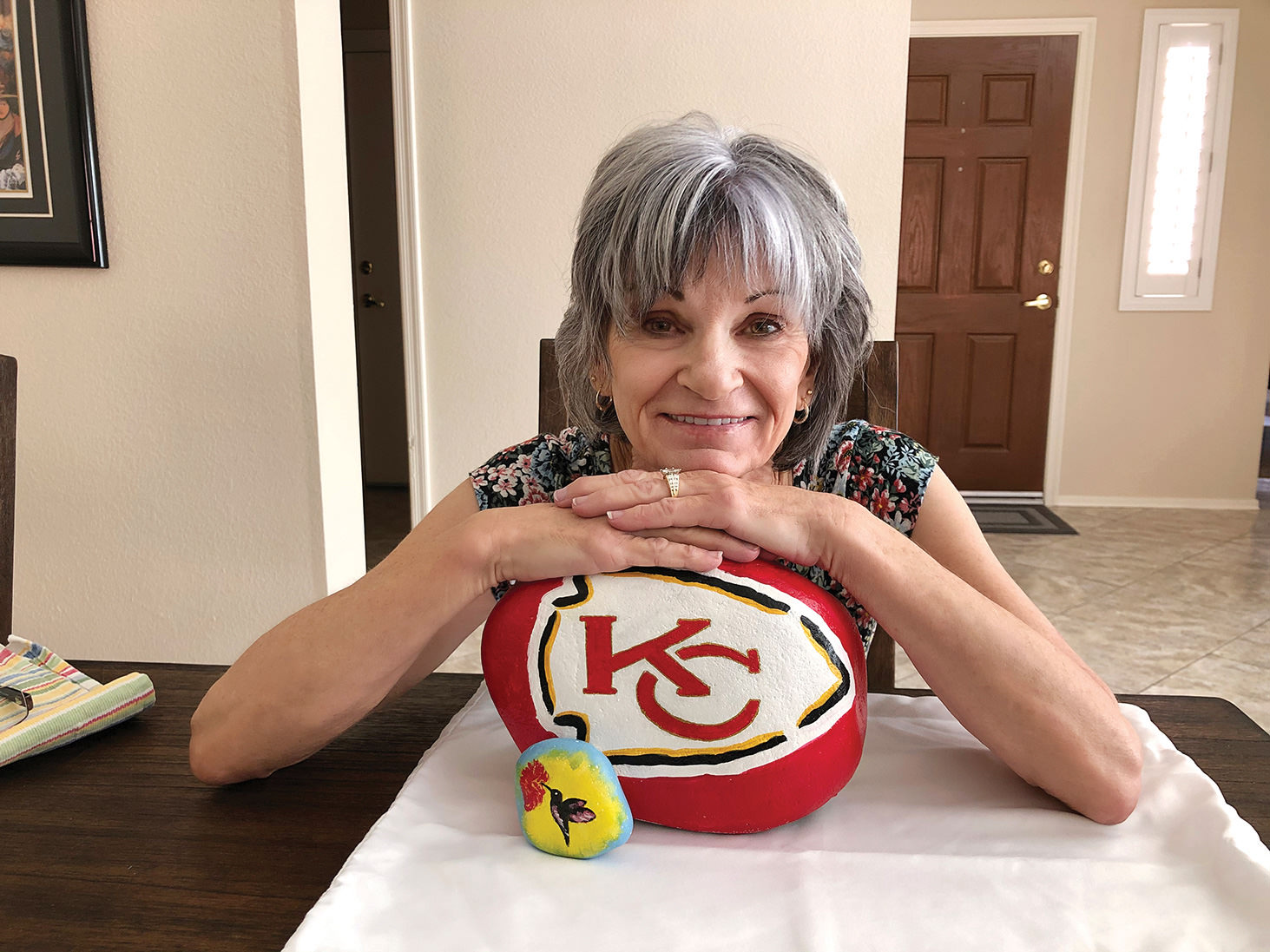 Sun Lakes resident Diane Haver has turned a pandemic hobby into a flourishing part-time job, painting logos of professional and college sports teams on stones from her backyard. Here she is shown with two of her specialties: a hummingbird and a logo of her favorite team, the Kansas City Chiefs. (Photo by Gary Vacin)