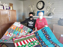 These are a few quilts made by Desert Threads members. Nancy Bonngard (right) presented 18 quilts recently to Nayre (left) at My Sister's Place.