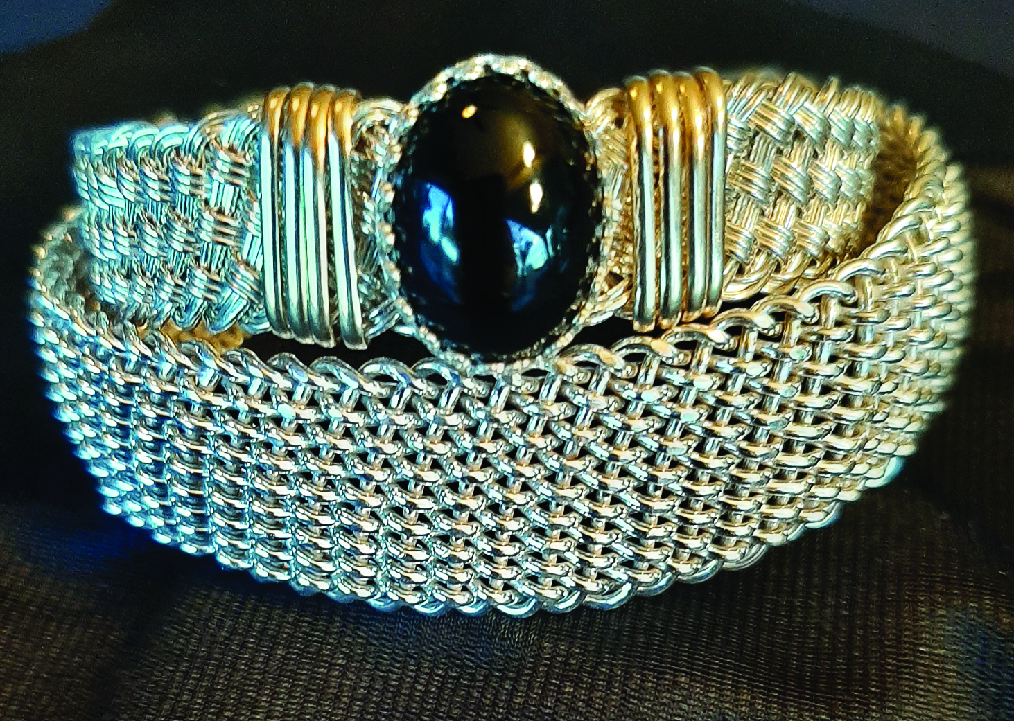 Bracelets by Henry Huss: The bottom is an 18-strand, 18-gauge, sterling silver wire weave. The top bracelet is a weave using 22-gauge sterling silver wire with gold wrap and an onyx stone.