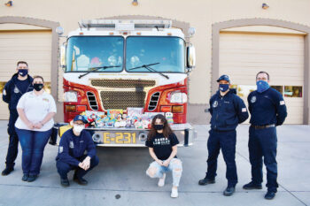 Pictured with the firefighters and medics of Sun Lakes Station 231 are (left to right) Firefighter Ryan Krause, Ms. Chiaramonte, Firefighter Matt Nasr, Basha student and president of the high school's Leo Club Megan Fought, Engineer Evan Mackenzie, and Paramedic Ari Barr. Basha's Leos are affiliated with the SunBird Lions Club. (Photo by Brian Curry)