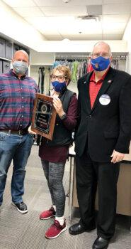 Jon Lyons and Terrie Sanders present the plaque to Humphrey Elementary Principal Luke Hickey.