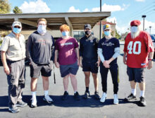 Hamilton High School football players flanked by Rotary members Bill Crump (left) and Roger Edmonds (right)