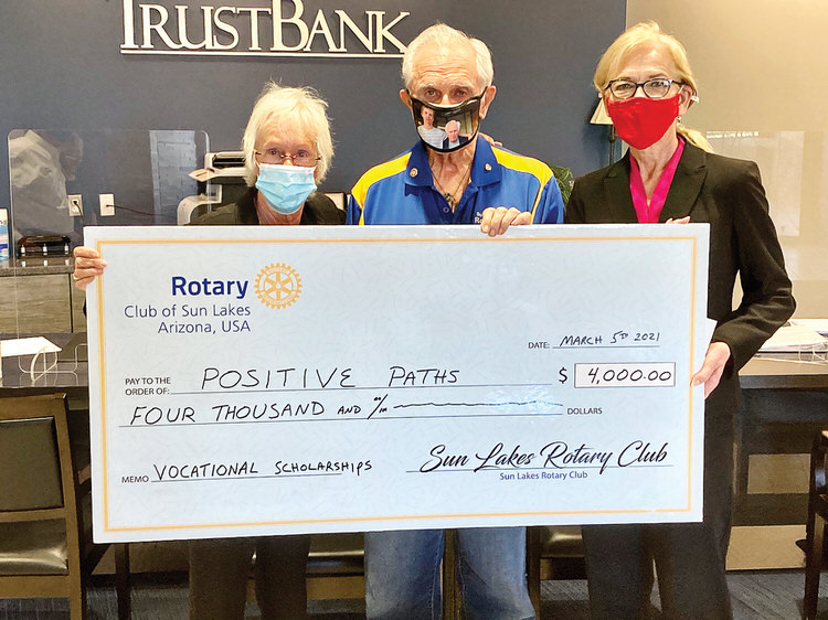 Sun Lakes Rotary members Marie Fotino and Howard Rudge present a check to Sandra Hudson from Trust Bank and a Positive Paths board member.