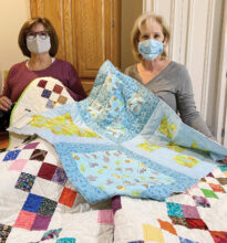 Blanca Sanchez and Jody Edwards hold a few of the colorful quilts made for children in area shelters.
