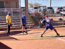 Slugger Mike Lebet prepares to swing at a recent Sun Division game. Catcher Dave Armstrong and umpire Ken Brenden look on. (Photo courtesy of Well Focused Fotos)