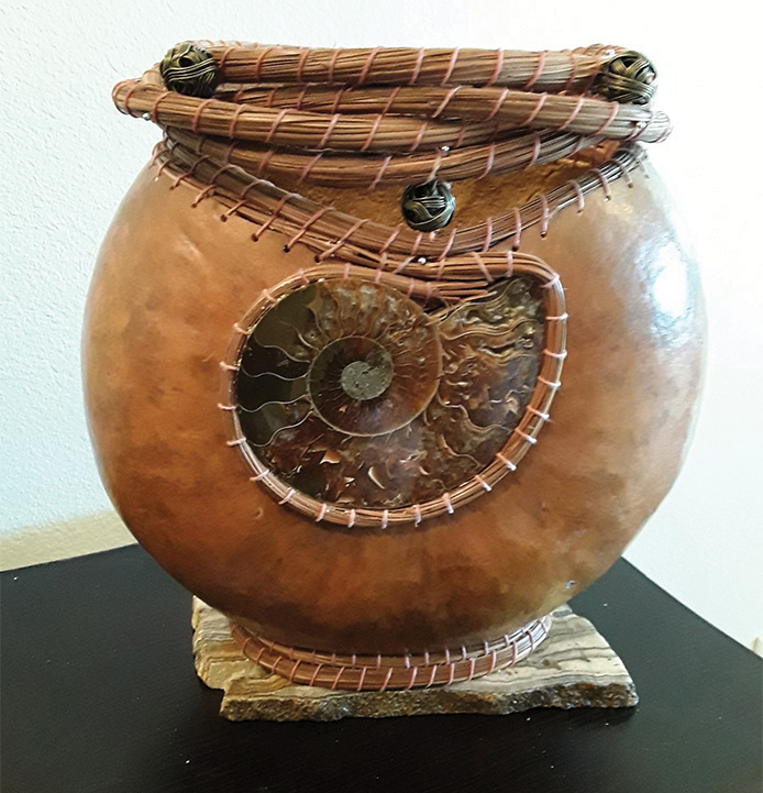 This gourd features an ammonite embellishment and pine needle weaving. It was created by one of our members at a class with Vicki Echols, during the Wuertz Gourd Festival in February of 2019.